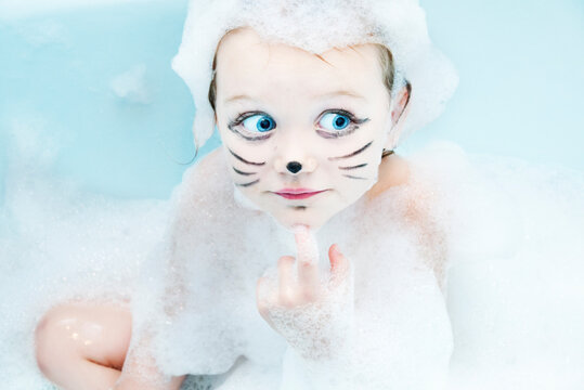Portrait of a girl with whiskers drawn on her face sitting in the bath covered in soap suds
