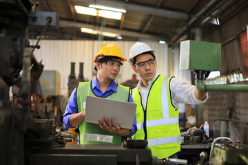 Fototapeta Asian engineering manager and mechanic worker in safety hard hat and reflective cloth using lathe machine inside the factory obraz