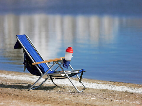 Lounge Chair On A Beach Next To A Lake In A Relaxing Setting.