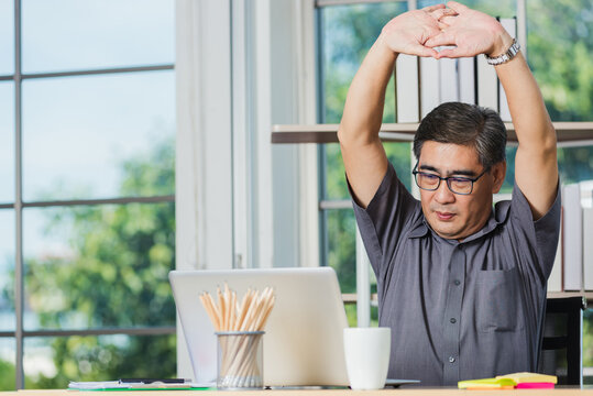 Asian businessman tired overworked he stretch oneself on the desk. senior man with eyeglasses break stretching his arms on table at his working place