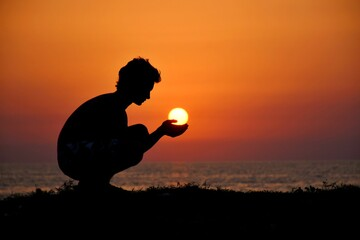 Optical Illusion Of Silhouette Man Holding Sun Over Sea During Sunset