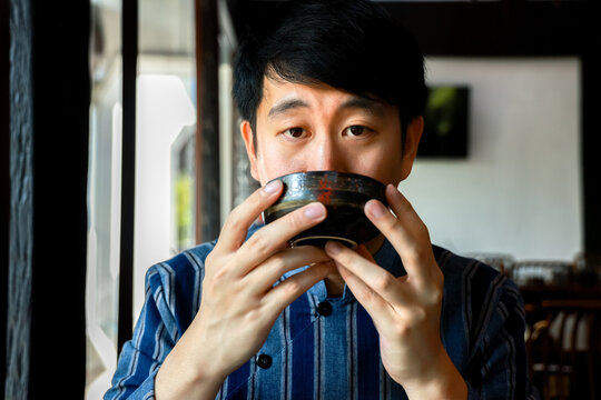 Young adult Chinese man in traditional costume drinking a cup of hot tea in Chinese restaurant. Mindful Asian guy has a sip of refreshening drink near window at cafe.