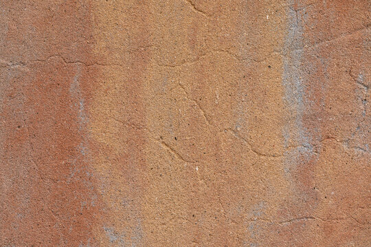 Horizontal close-up image of a cracked stucco wall painted in southwestern style colors, a useful image for copy space.