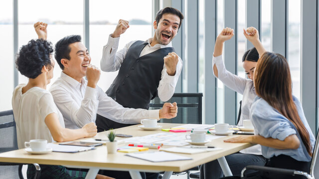 Group of five diversity businessmen, two men and three women sitting at meeting desk. They excited and greeting for good news and success result of their team.