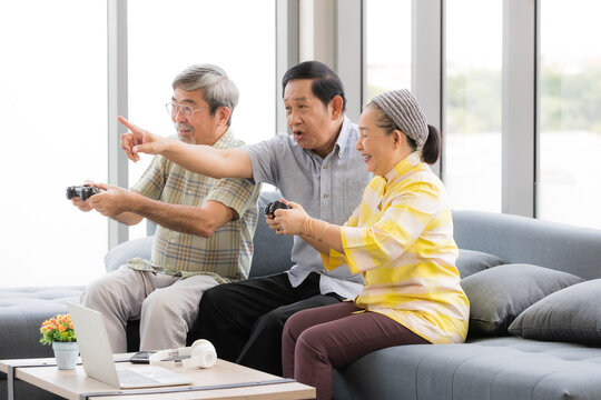 A group of three senior Asian people, grandparents join together and exciting during playing game. Concept for happiness lifestyle and learning for new technology of the older generation