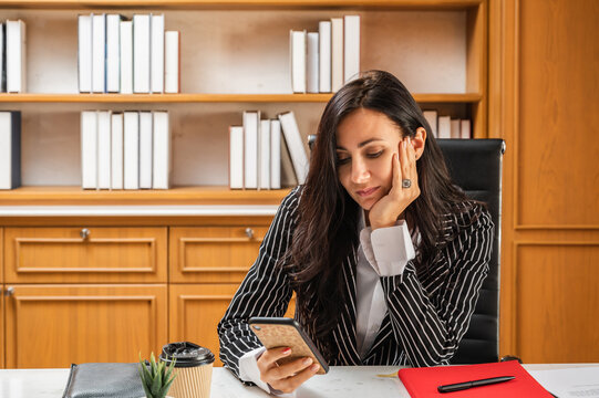 A young businesswoman or lawyer sitting at her desk in the office with a hand on her face and looking bored using a mobile phone device.