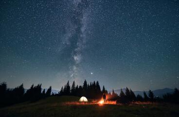 Silhouette of male traveler near illuminated camp tent under beautiful night sky with stars....