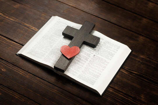 Open book Bible. Wooden cross of Jesus. A heart. On a wooden table.