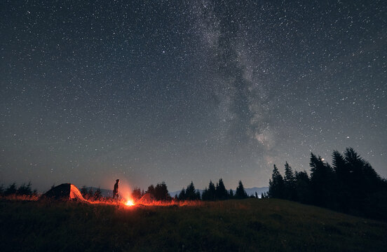 Male hiker standing near campfire and tent under beautiful night sky with stars. Magnificent view of blue starry sky and Milky way under grassy hill. Concept of travelling, hiking and night camping.