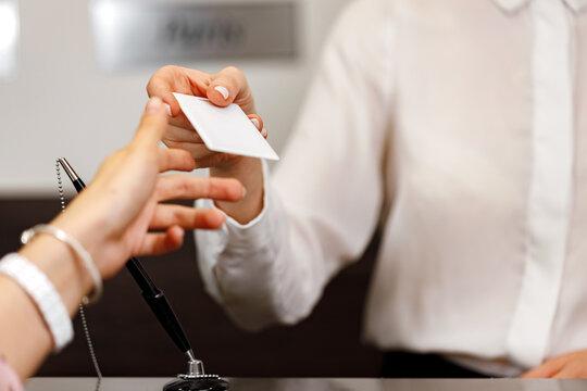 Woman receiving door key in hotel front desk