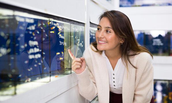 Young woman choosing aquarium fish while shopping in pet store