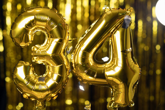 The golden number 34 thirty four is made of an inflatable balloon on a yellow background. One of the complete set of numbers. Birthday, anniversary, date concept