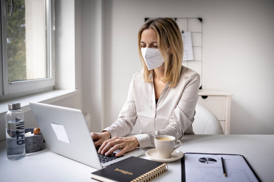 Corona office challenge, business woman wearing ffp2 mask working on laptop in office
