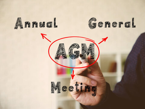 AGM Annual General Meeting on Concept photo. Young bussines man in a suit writing on an background.