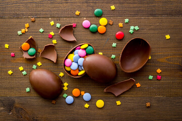 Happy Easter with chocolate eggs and sweets, top view