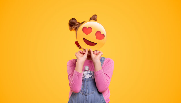 Kid hiding face behind emoticon
