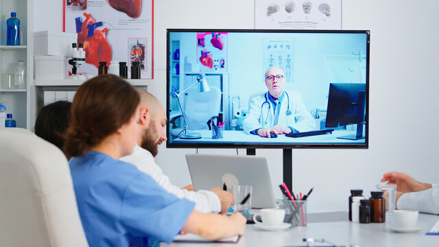 Concentrated purposeful experienced medical team holding online video meeting with senior doctor on interactive screen. Team of specialists discussing diagnosis of patients uing video conference