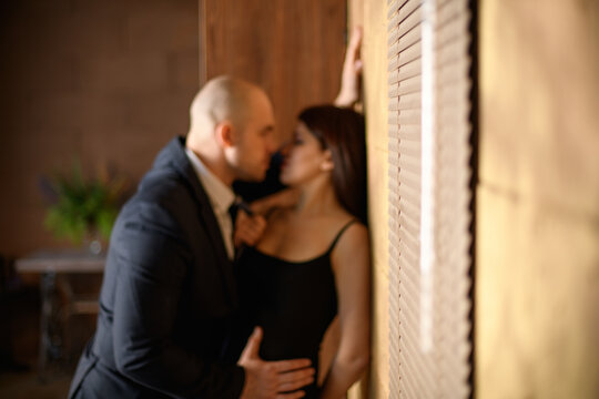 Blurred background. A couple in love. A bald man in a suit hugs a woman in a black dress against the wall. The girl pulls the guy by the tie.