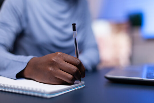 Close up of dark skinned woman taking notes while working from home office sitting at desk comp. Black freelancer respecting deadline studying late at night.