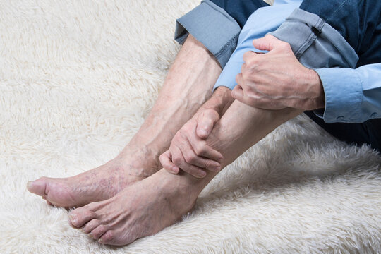 Ankle disease, arthritis or arthrosis. Cropped shot of elderly man sitting on sofa and suffering from leg pain.