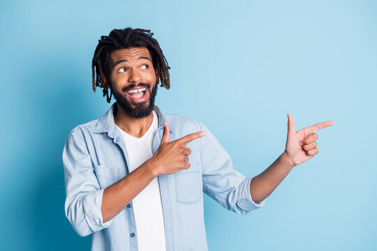 Portrait of attractive cheerful guy demonstrating copy space good offer solution isolated over bright blue color background