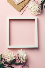 Creative flat lay with flowers, notebook, glasses, mobile phone and white wooden frame on pink...