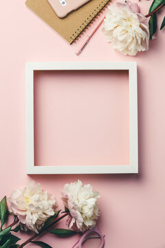 Creative flat lay with flowers, notebook, glasses, mobile phone and white wooden frame on pink background