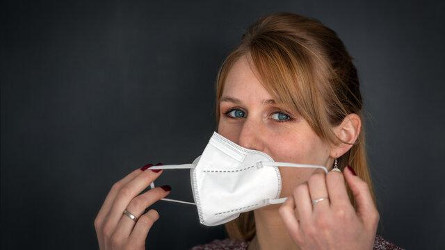 Junge rot blonde Frau zieht sich eine FFP2 Maske zum Schutz vor Ansteckung mit dem Coronavirus bzw. Covid-19 an, Nahaufnahme isoliert vor dunklem Hintergrund