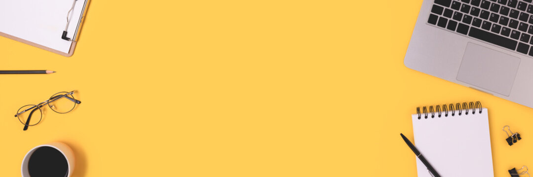 Banner with laptop and office supply on a yellow background with copy space. Online business workspace, distance education, e-learning concept.
