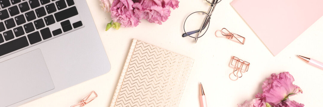 Banner with laptop, flowers and office supply on a beige background. Feminine workspace for online work.