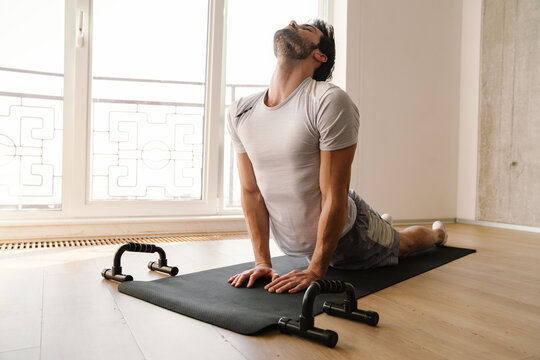 Focused athletic man stretching his body while working out at home