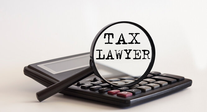 Focused on TAX LAWYER concept. Magnifier glass with text on calculator. Business concept