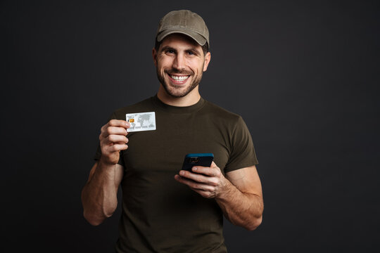Smiling military man posing with cellphone and credit card