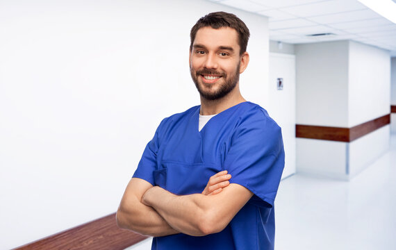 healthcare, profession and medicine concept - happy smiling doctor or male nurse in blue uniform with crossed arms over hospital corridor background