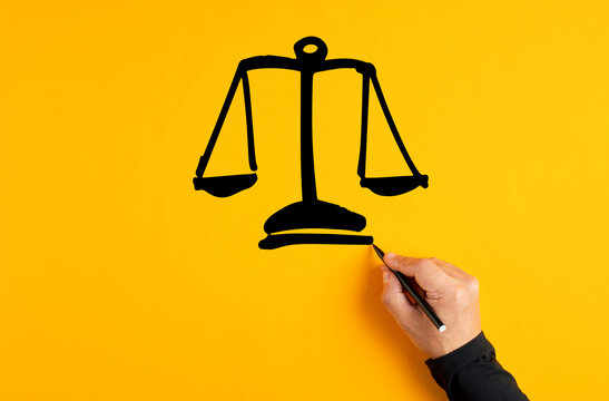 Male hand drawing a justice scale on yellow background. Fairness, equality or trust