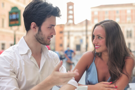 Young man and woman talking in outdoor café