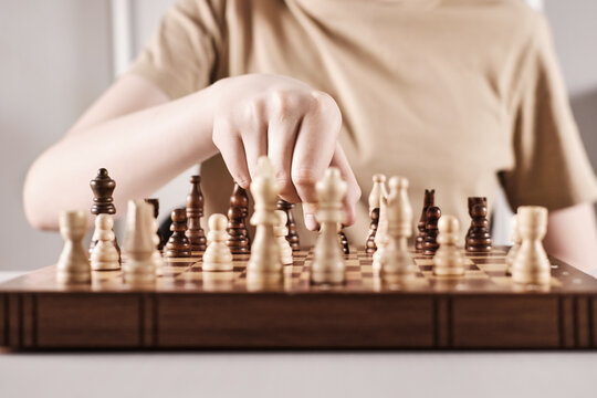 Hand holds chess piece and makes a move. Faceless boy develops game strategy, selective focus on hand