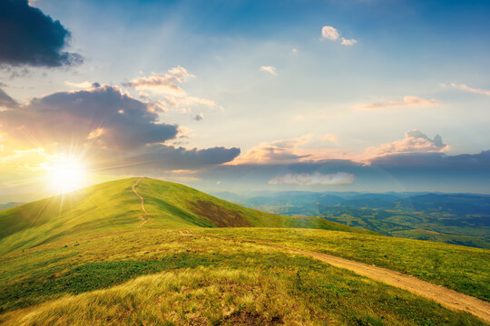 mountain landscape on a bright spring sunset. path through meadow in grass on the hill in evening light. wonderful weather with fluffy clouds on the sky. borzhava ridge of carpathians