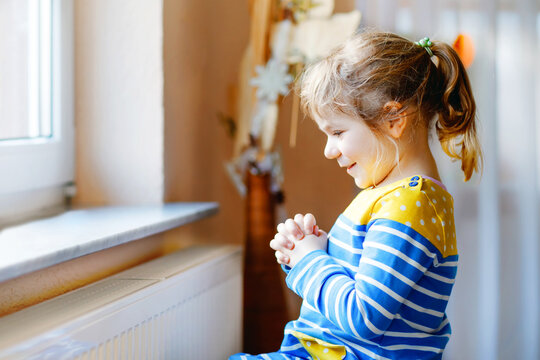 Cute toddler girl praying to God at home. Child using hands for pray and thank Jesus. Christian tradition.