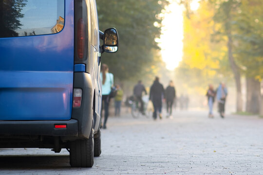 Passenger van car parked on a city alley street side with blurred walking pedestrians in autumn.