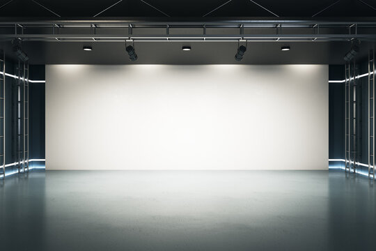 Big blank light screen instead of wall with projectors in empty industrial style hall room with glossy floor. Mockup. 3D rendering.