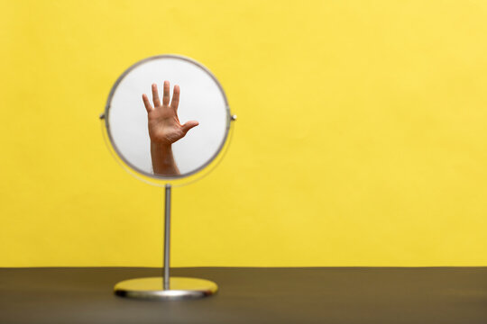 The reflection of a human hand in a round mirror on a yellow background.