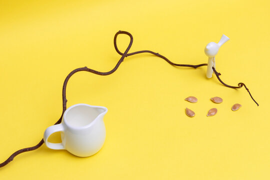 Minimalist composition of white tableware. toys of birds, dry twigs and seeds on a yellow background.