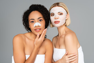 Fototapeta Multiethnic women with cleansing stripe and sheet mask looking at camera isolated on grey