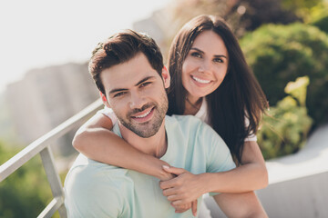 Photo of positive attractive couple embrace piggybacking toothy smile wear casual clothes street...