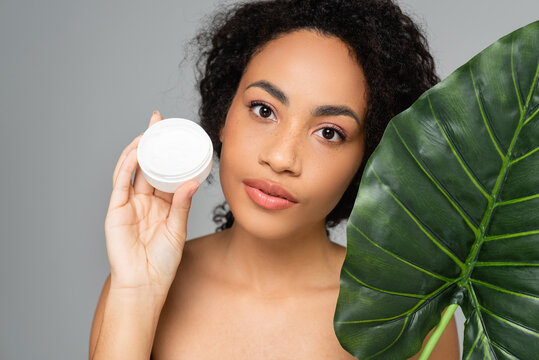 African american woman with perfect skin holding tropical leaf and cosmetic cream isolated on grey