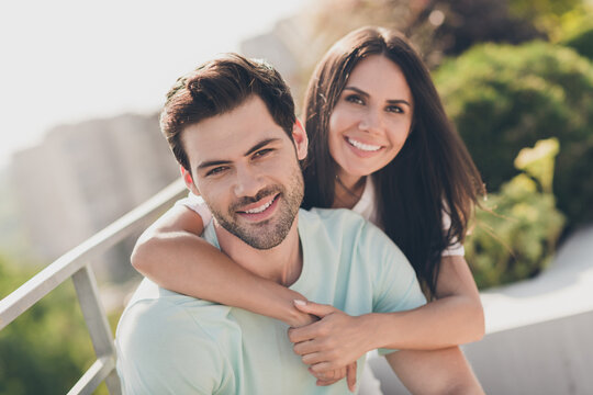 Photo of positive attractive couple embrace piggybacking toothy smile wear casual clothes street outdoors