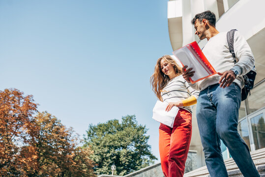 Two young students talking to each other during descend the stairs at the university outside. Two colleagues smiling, a young woman and a man going to the college campus together.