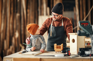 Obraz Father and son making bird house in workshop - fototapety do salonu
