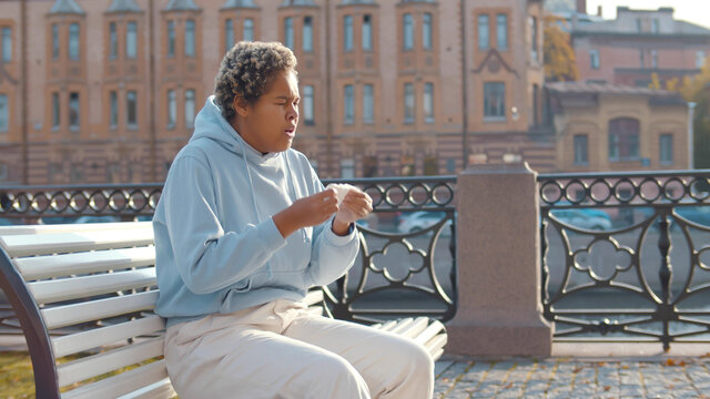 Young ill african american coughing and sneezing in napkin outdoor sitting on bench.
